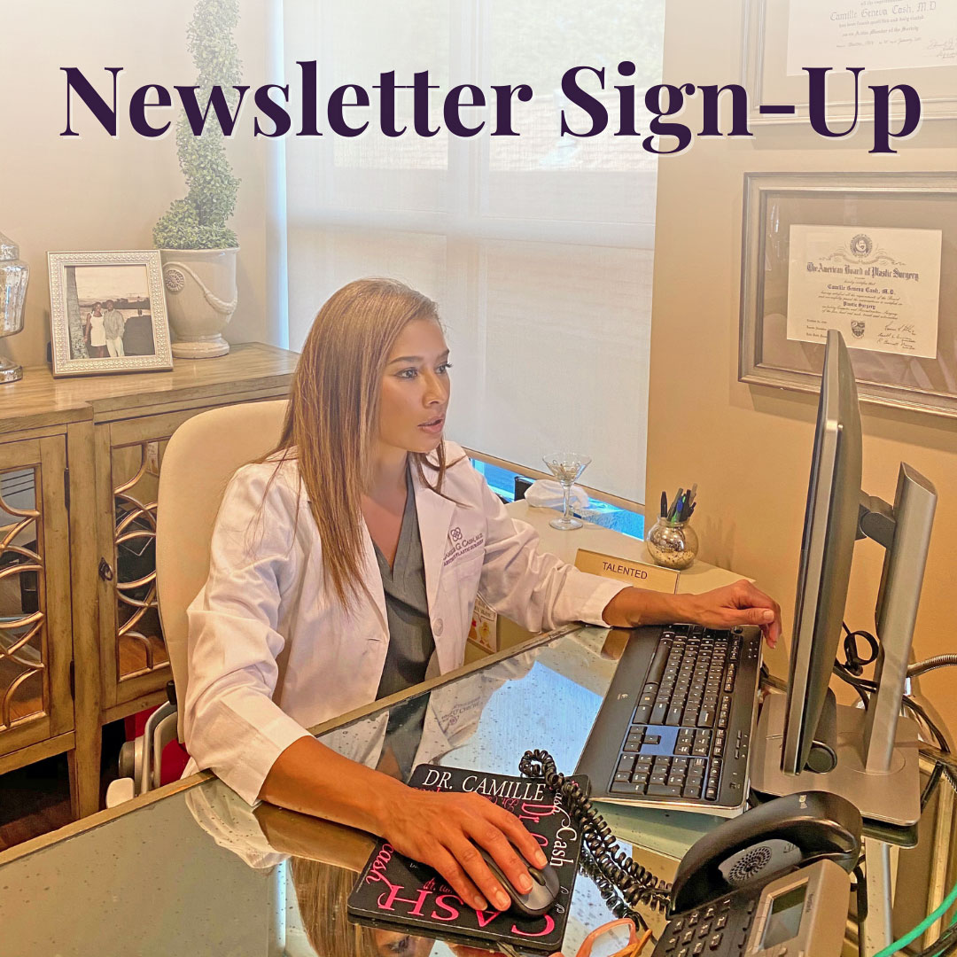 Double Board Certified Plastic Surgeon Camille Cash MD sitting at her desk typing a newsletter for Houston patients to sign up.